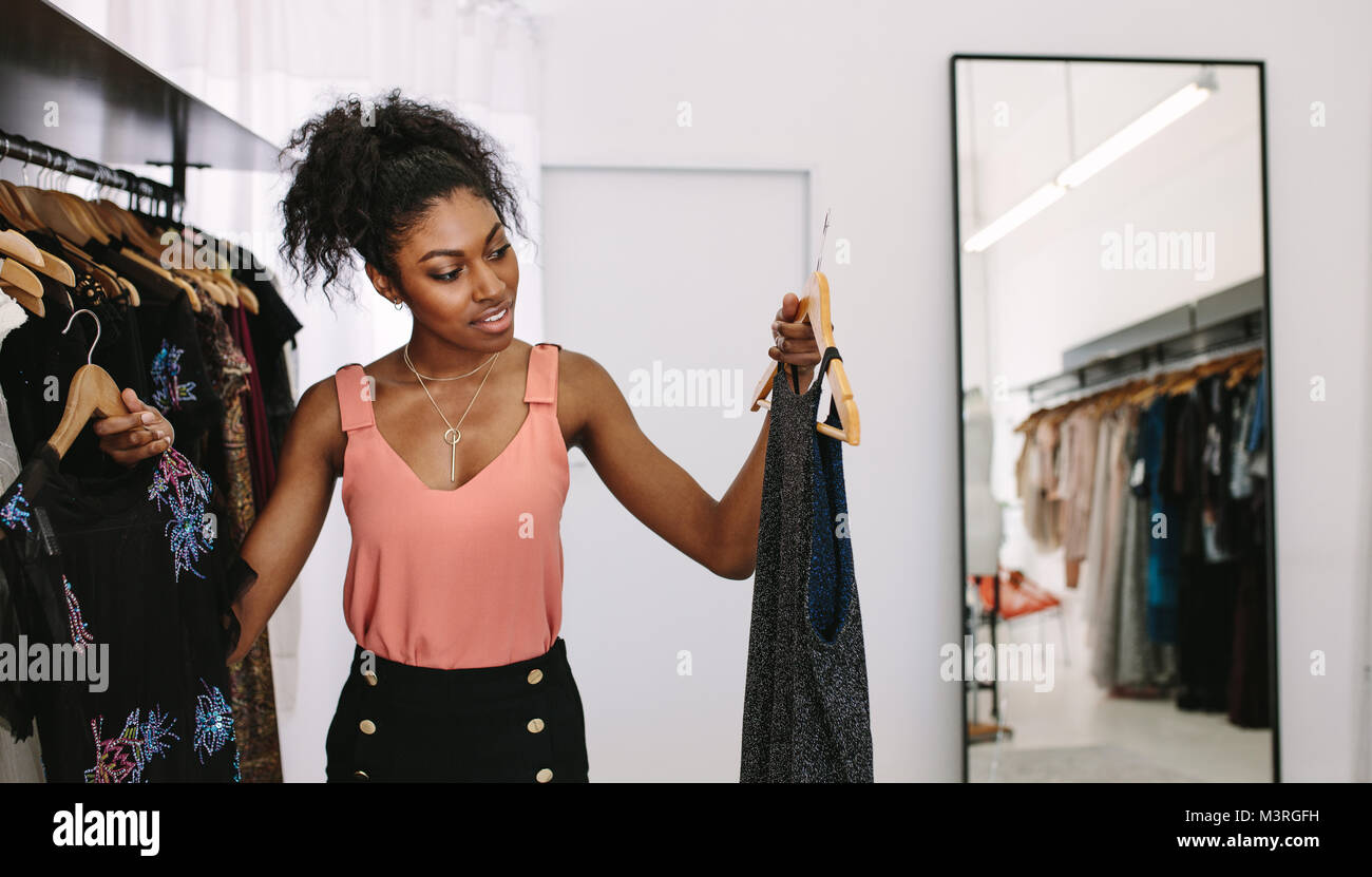 Female fashion designer looking at designer dresses in her fashion studio. Customer comparing dresses in a fashion - Stock Image