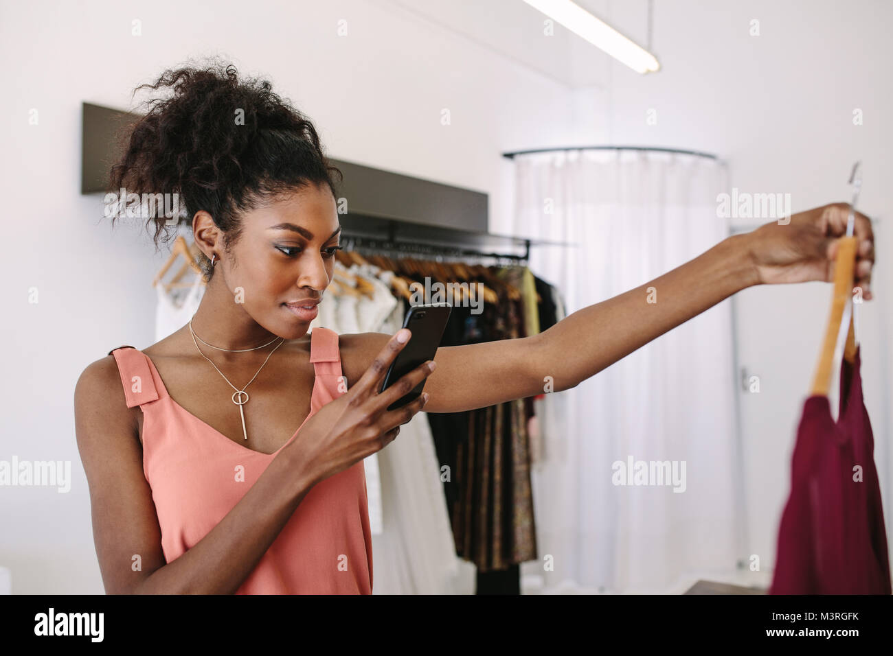Fashion designer taking photograph of a designer dresses in her fashion studio. Customer taking photograph of dress - Stock Image