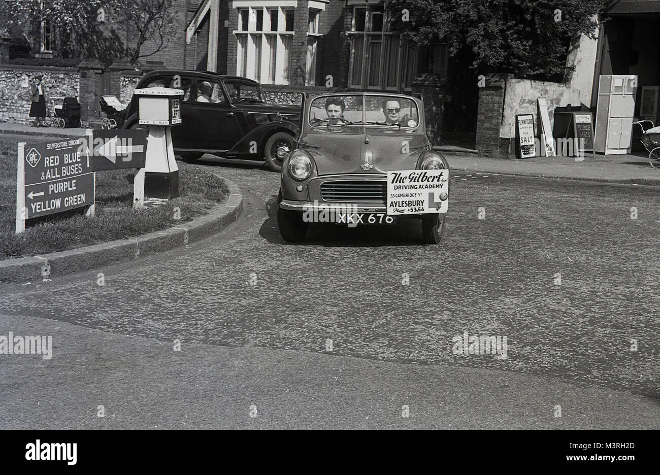 1955, historical, young lady turning a corner whilst having a driving lesson in an open-top two door Morris Minor - Stock Image