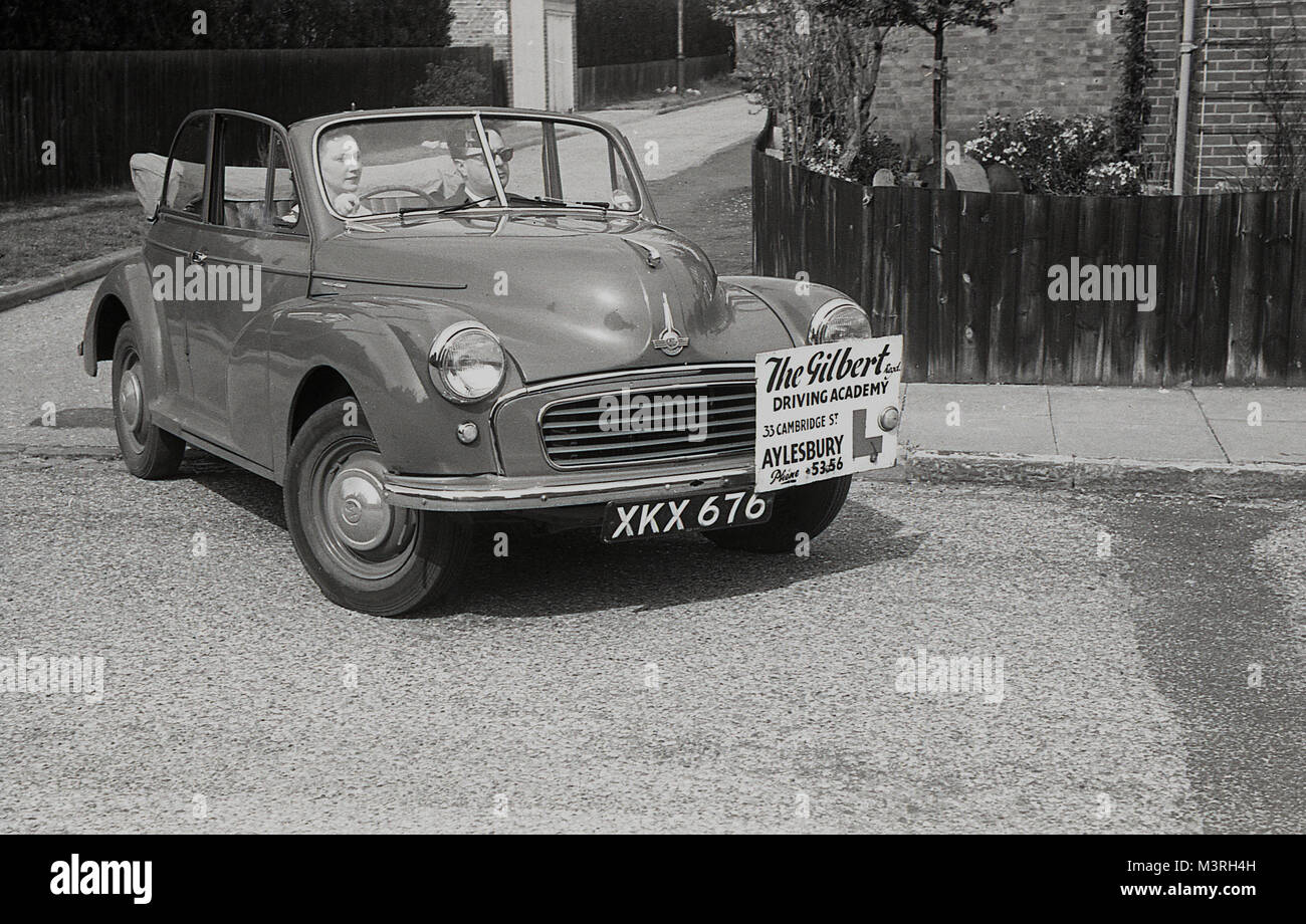 1955, historical, young lady having a driving lesson in an open-top two door Morris Minor car with The Gilbert Driving - Stock Image