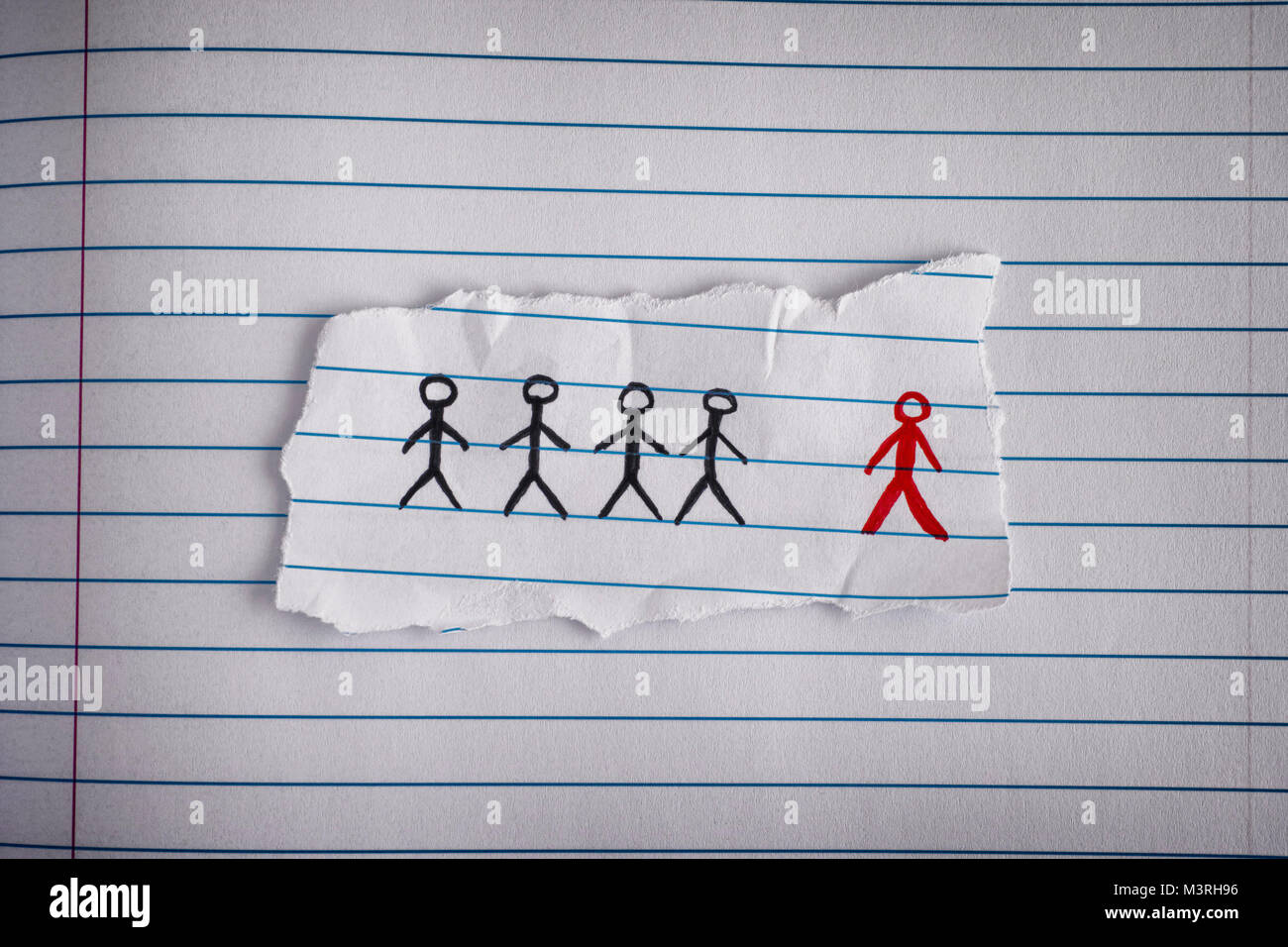 Piece of paper with drawn people and the red one is the odd one out. Concept Image. Close up. - Stock Image