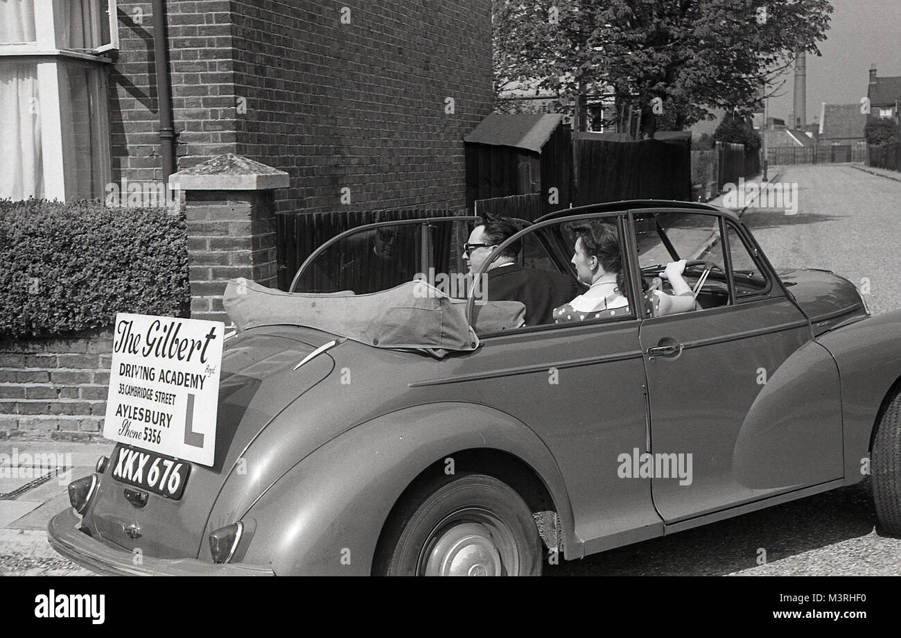 1955, historical, young lady reversing around a corner in an open-top two door Morris Minor car, whilst having a - Stock Image