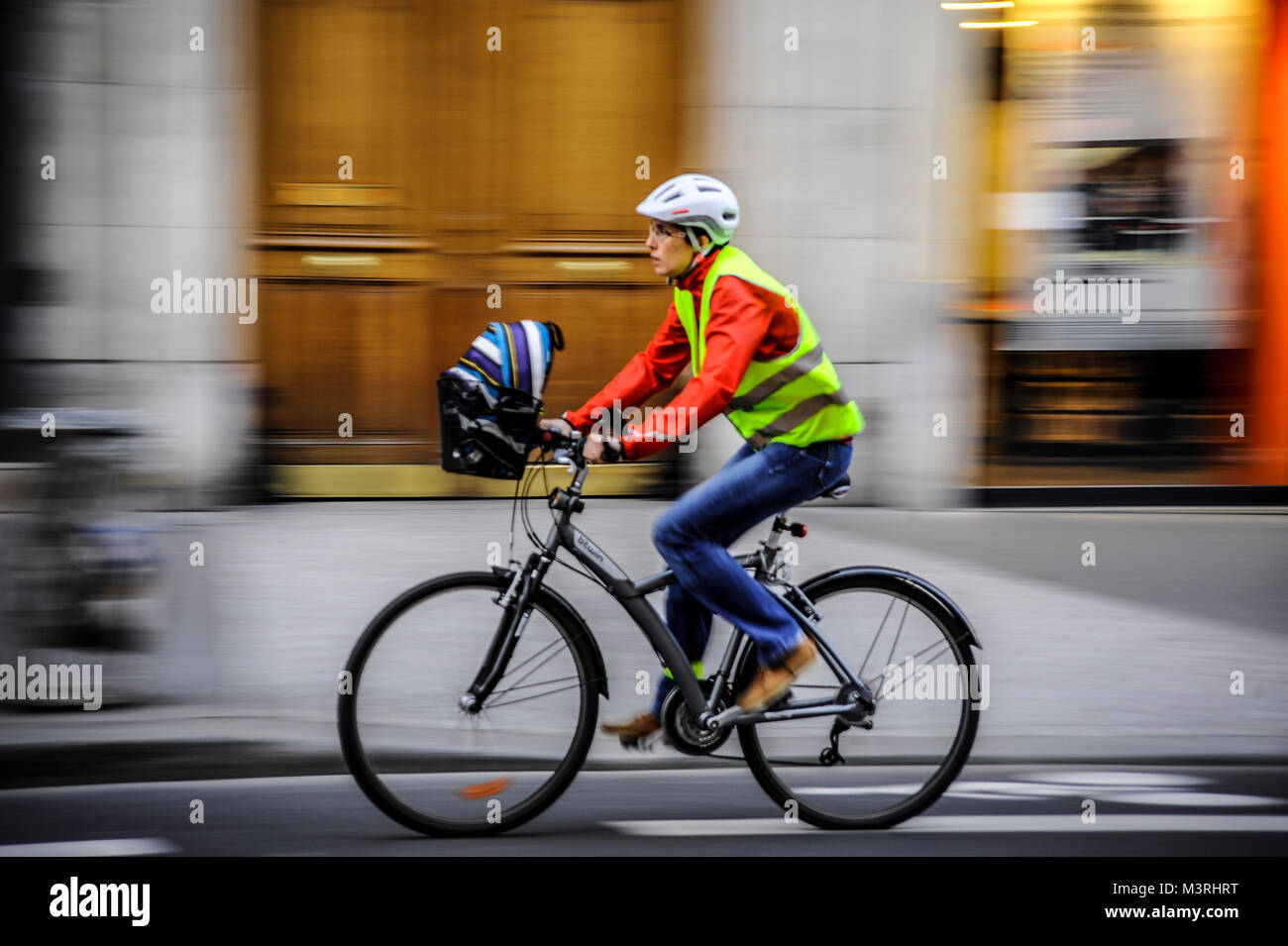 PARIS FRANCE - WOMAN ON BICYCLE DRESSED WITH A HELMET AND A SAFETY VEST PASSING BY RUE DE RENNES - PARIS BICYCLE - Stock Image