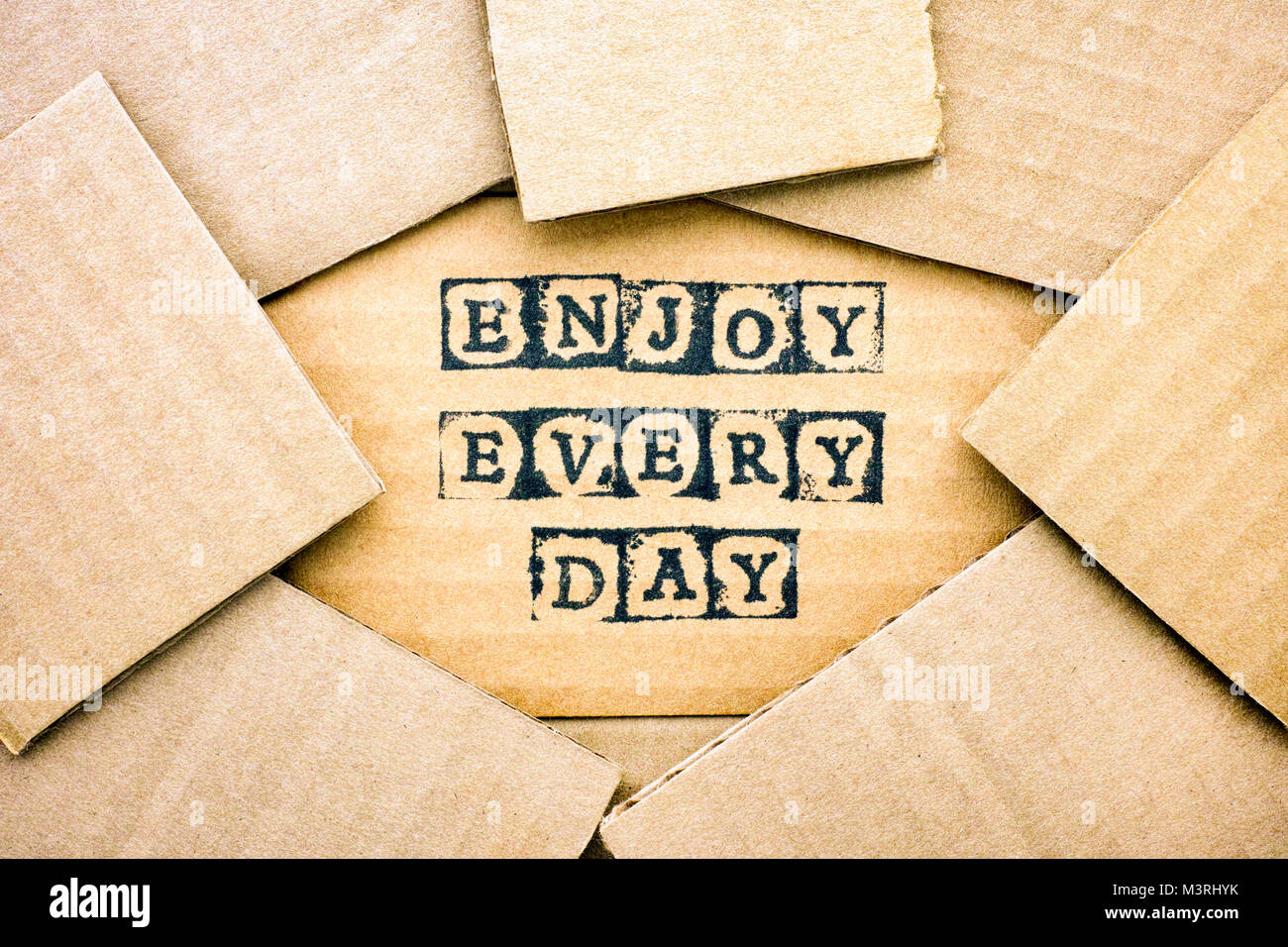 Words Enjoy Every Day make by black alphabet stamps on cardboard with some piece of cardboard. - Stock Image