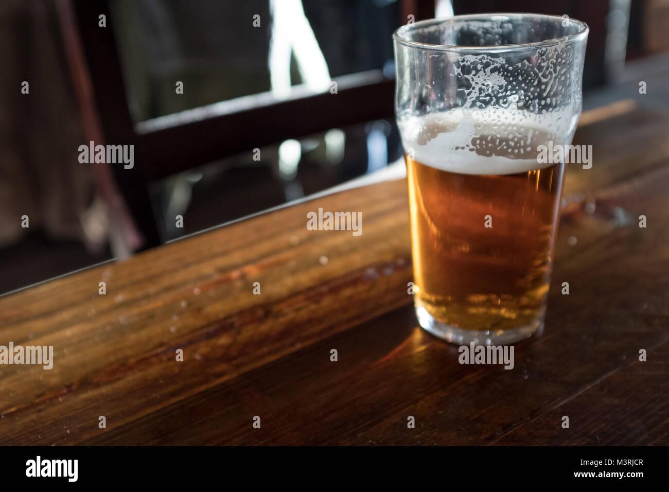 Half full pint of beer on pub table - Stock Image