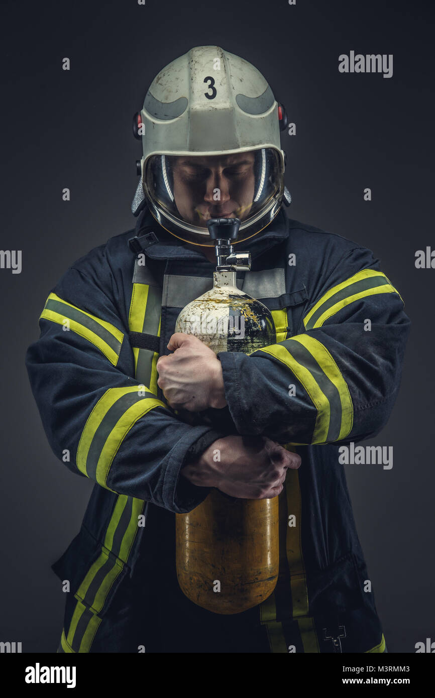 Firefighter rescue holds yellow oxygen tank.  - Stock Image