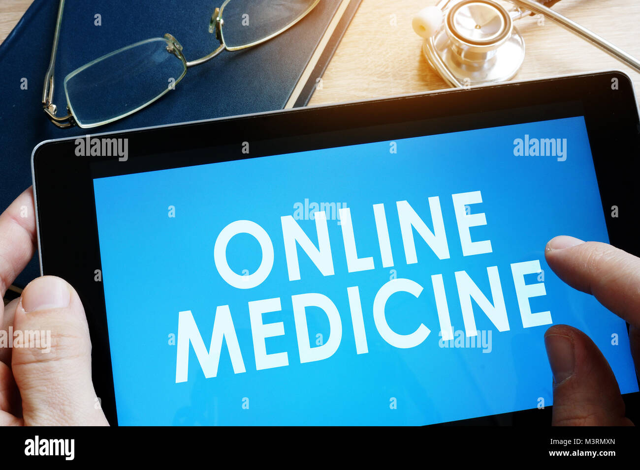 Doctor holding tablet with words online medicine. - Stock Image