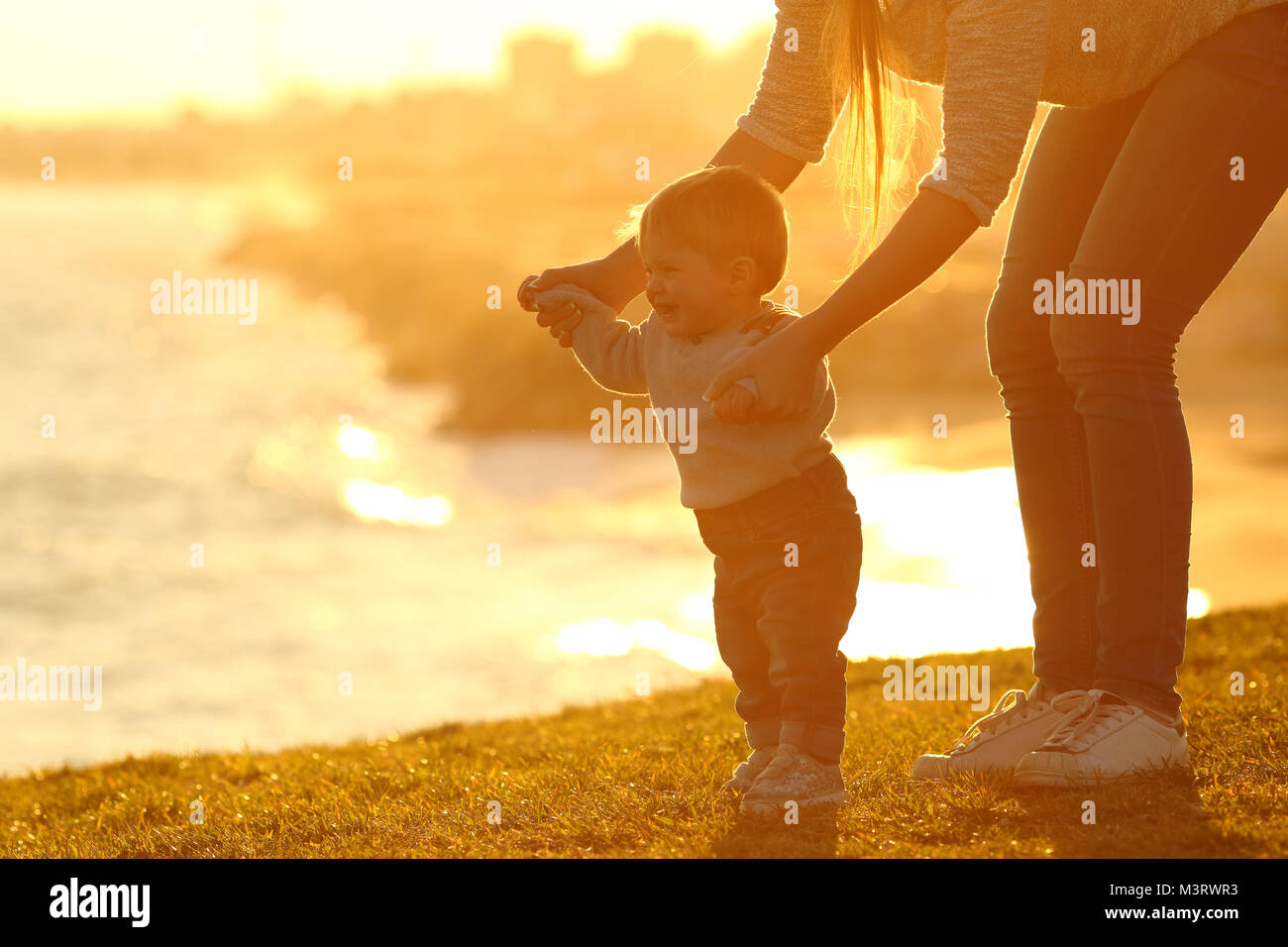 Side view of a kid learning to walk and mother helping him on the grass outdoors at sunset with a city in the background - Stock Image