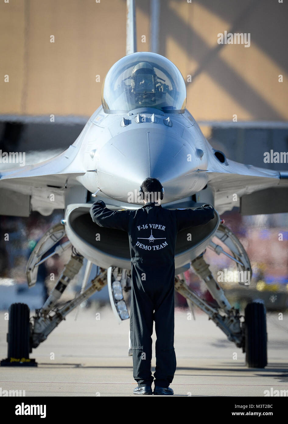 An F-16 Fighting Falcon is marshaled into position at Davis-Monthan Air Force Base on March 4, 2016. The F-16 was Stock Photo