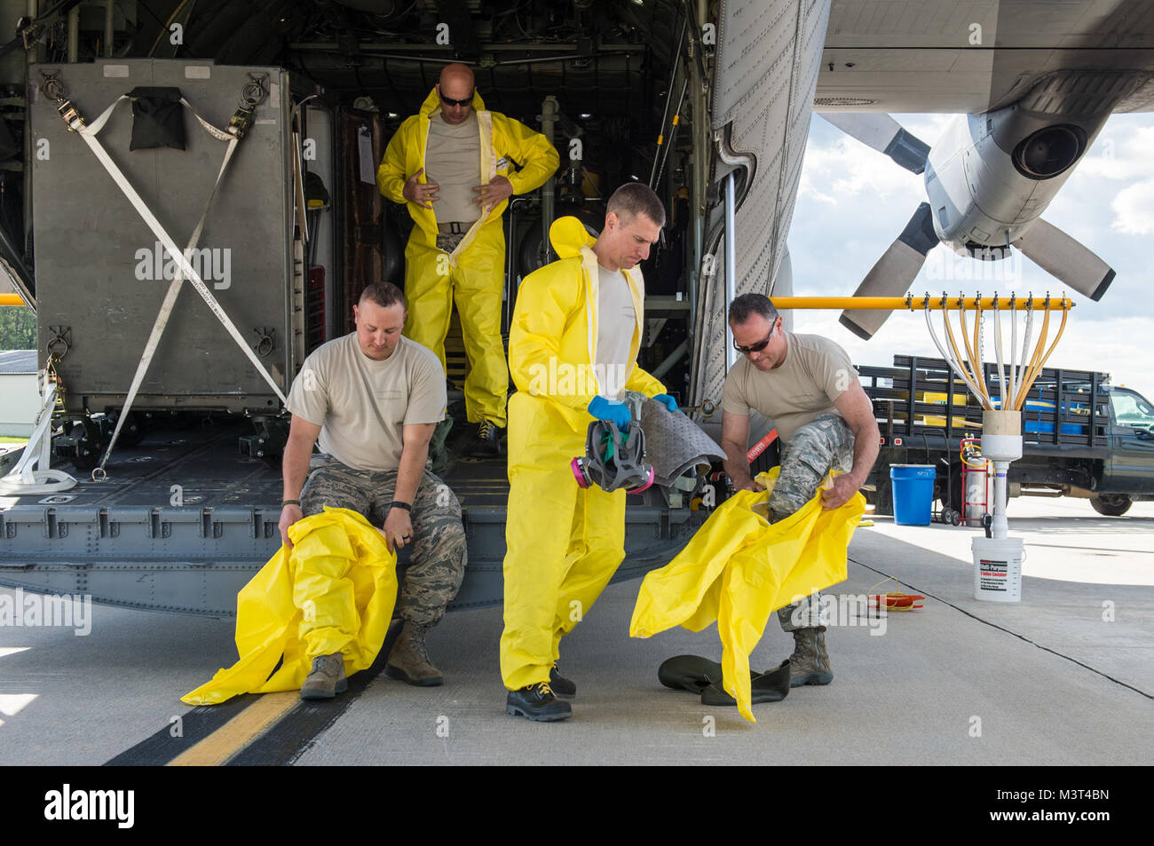 Aerial spray maintainers from the 910th Airlift Wing don personal protective equipment before loading mosquito insecticide - Stock Image