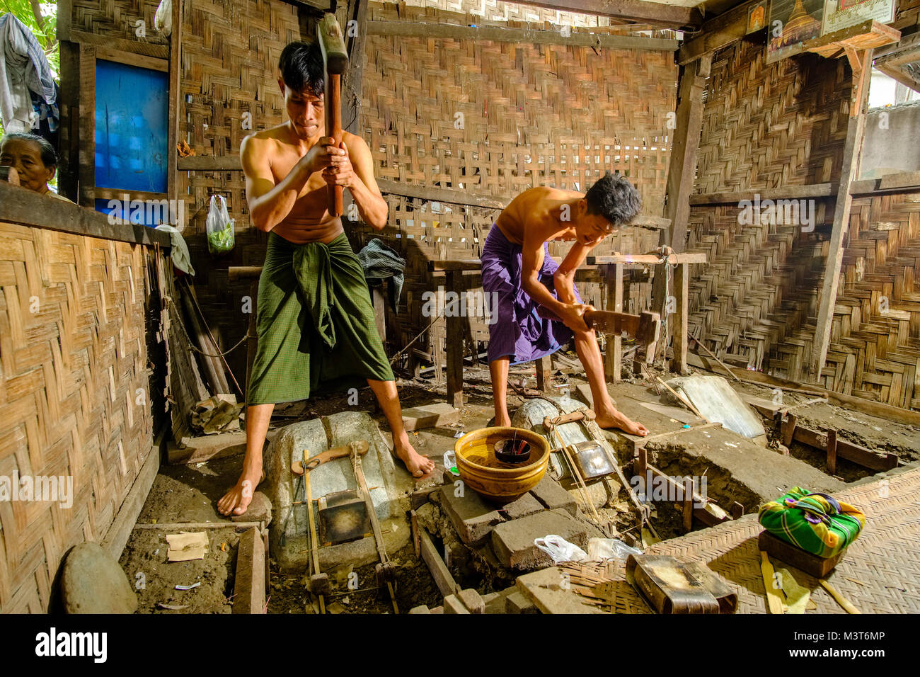 Workers are beating gold for religious offerings to very thin layers - Stock Image