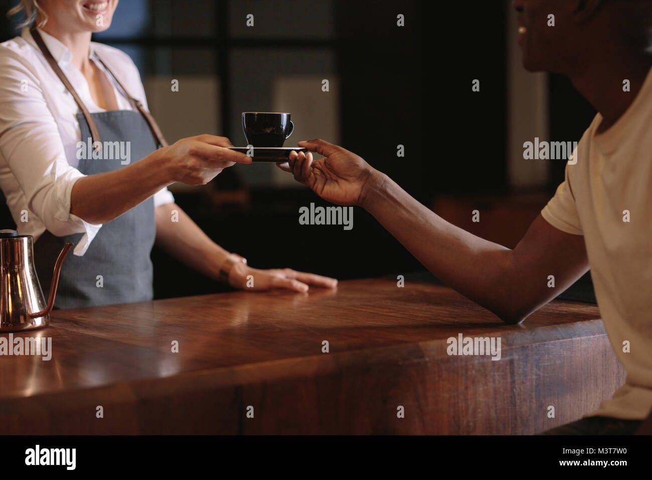 Woman serving coffee over the counter to a customer. Cropped shot of coffee shop owner handing over a cup of coffee - Stock Image