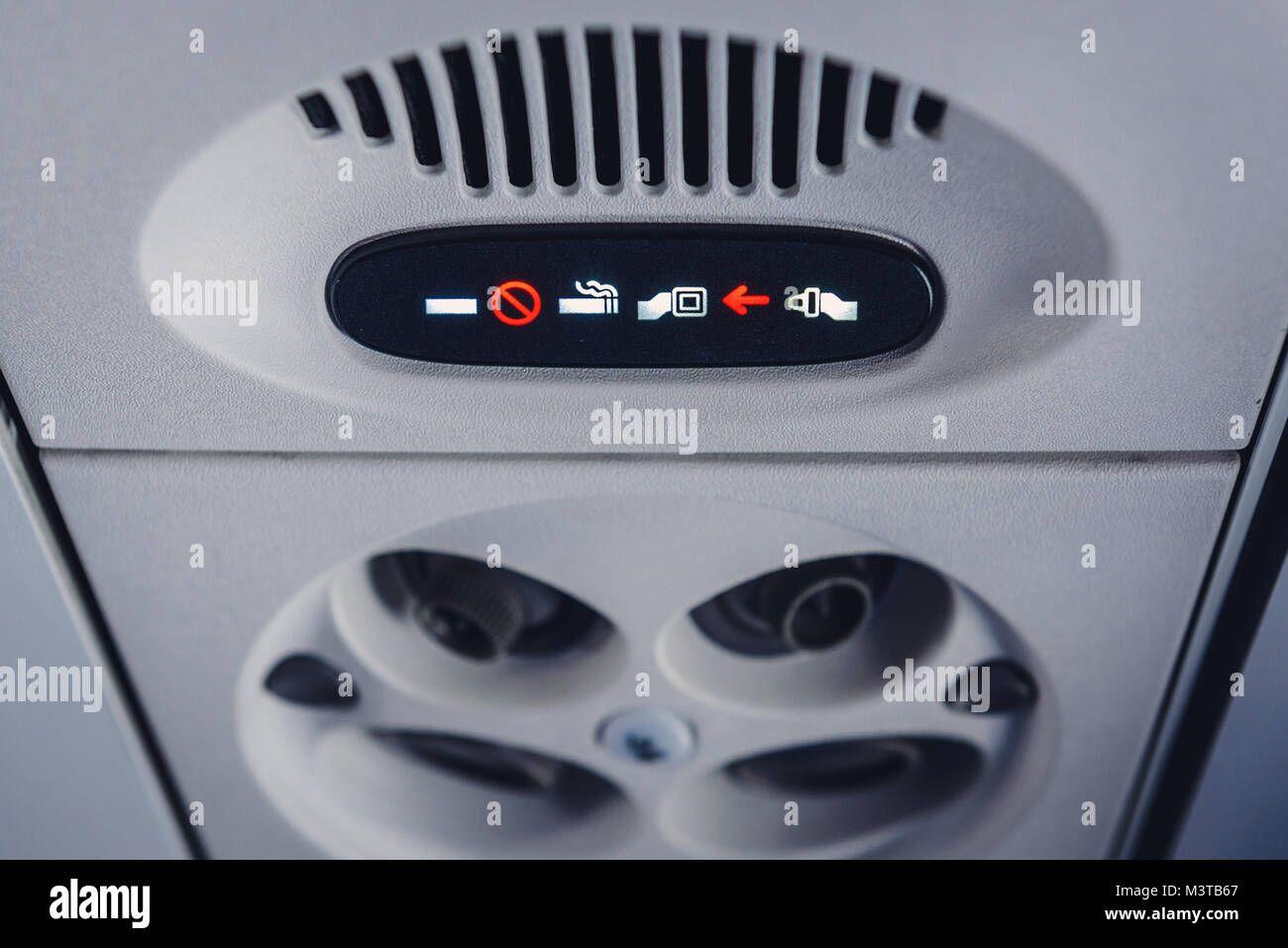 No smoking sign and fasten seat belts signs in plane during take-off - Stock Image