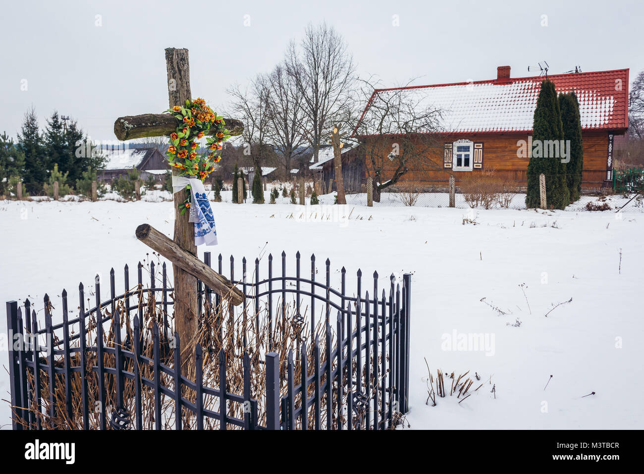 Old wayside cross in Soce village on so called The Land of Open Shutters trail, famous for traditional architecture - Stock Image