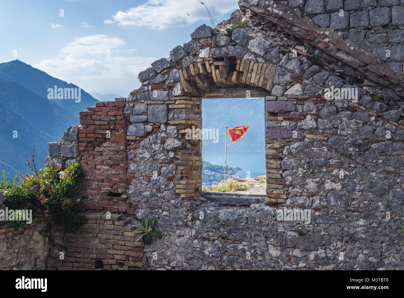 Flag among ruins of Saint John Fortress in Kotor coastal city, located in Bay of Kotor of Adriatic Sea, Montenegro Stock Photo