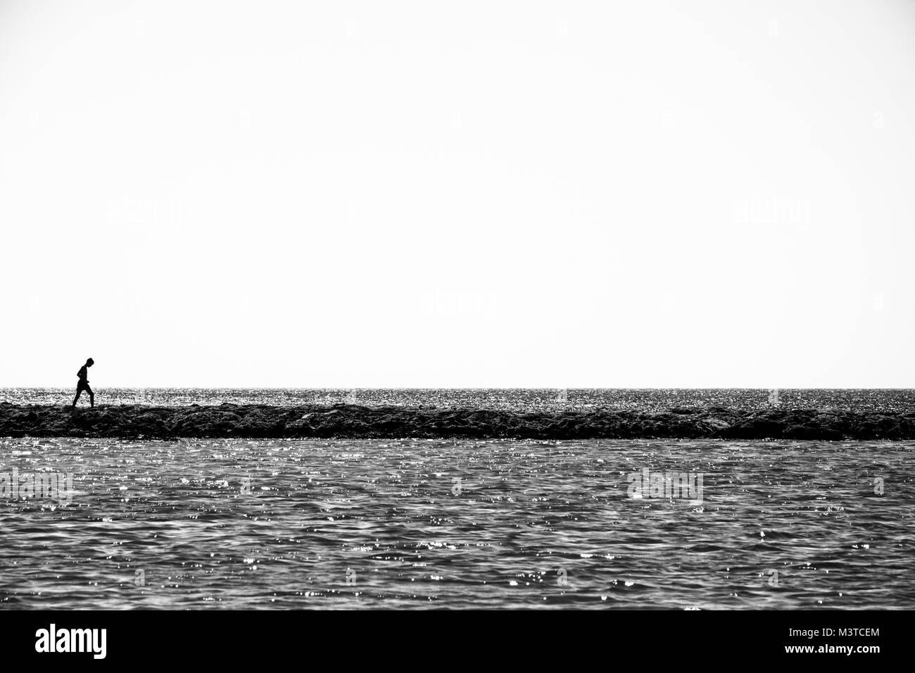 Lonely child walks on a thin coastline minimalistic black and white photo stock