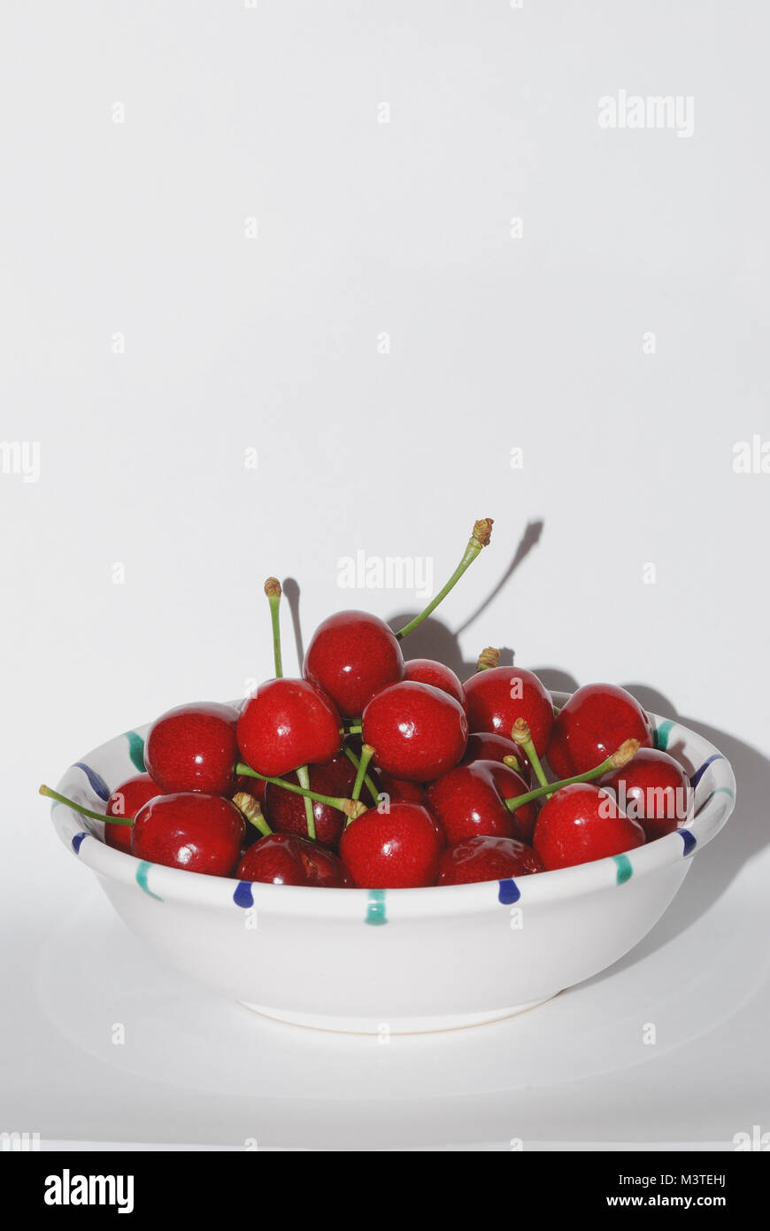 hochformat many juicy red cherries in a bowl - Stock Image
