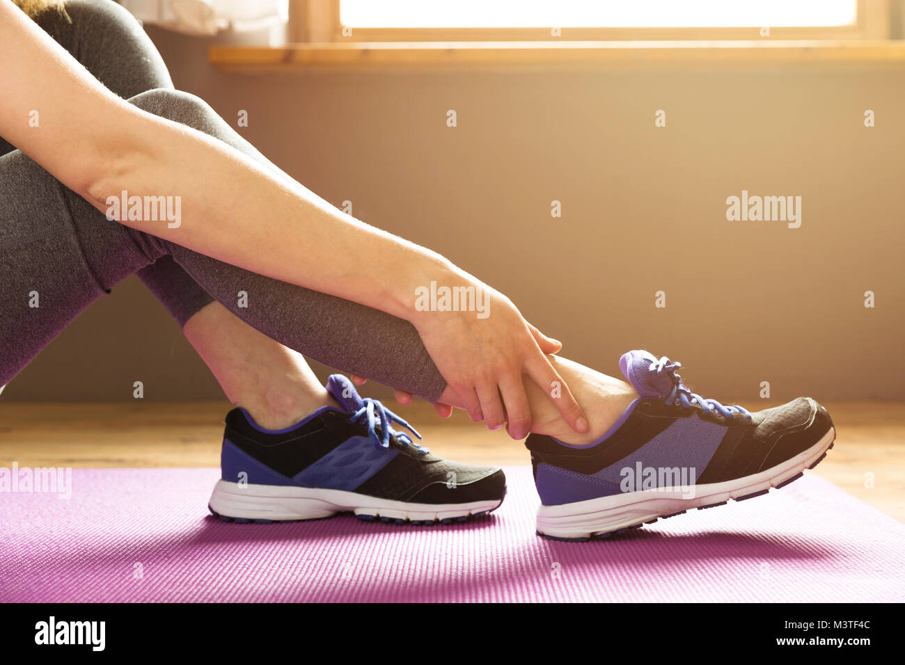 Young woman suffering from an ankle injury while exercising. Sport exercise injuries concept. - Stock Image