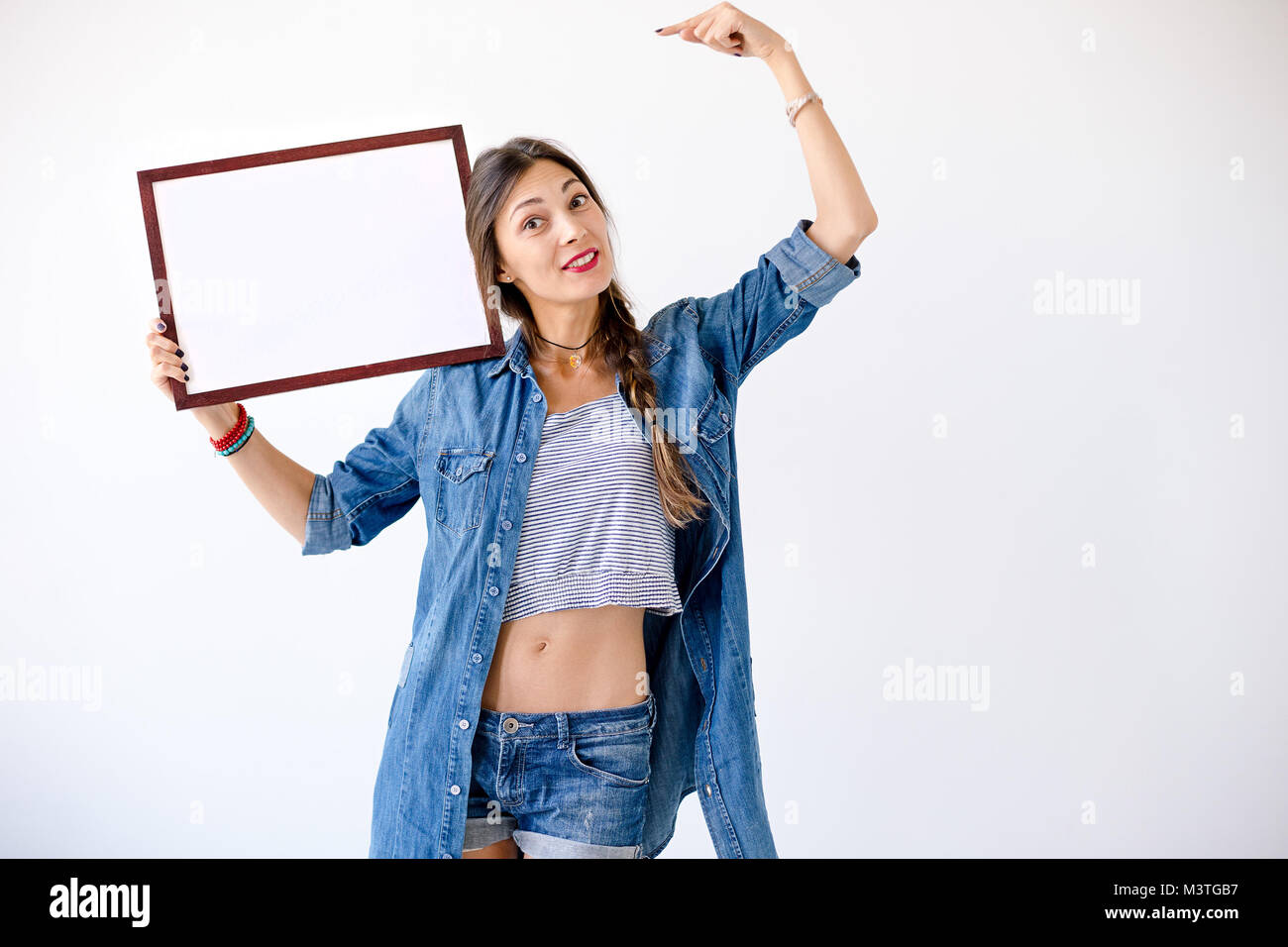 Body language concept - smiling young playful woman showing an empty right shoulder side display of a product for - Stock Image
