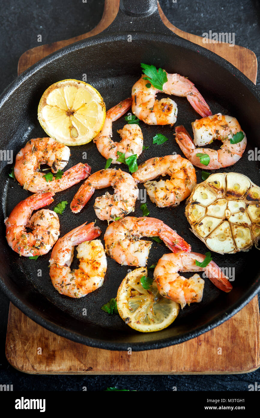 Roasted shrimps with lemon, garlic and herbs. Seafood, shelfish. Shrimps Prawns grilled with spices, garlic and - Stock Image