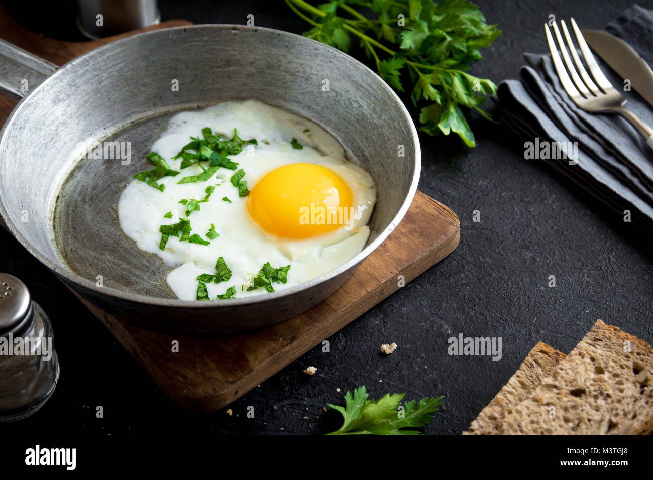 Fried Egg on Frying Pan for Breakfast. Fried egg with bread and parsley on skillet over black stone table, top view, - Stock Image