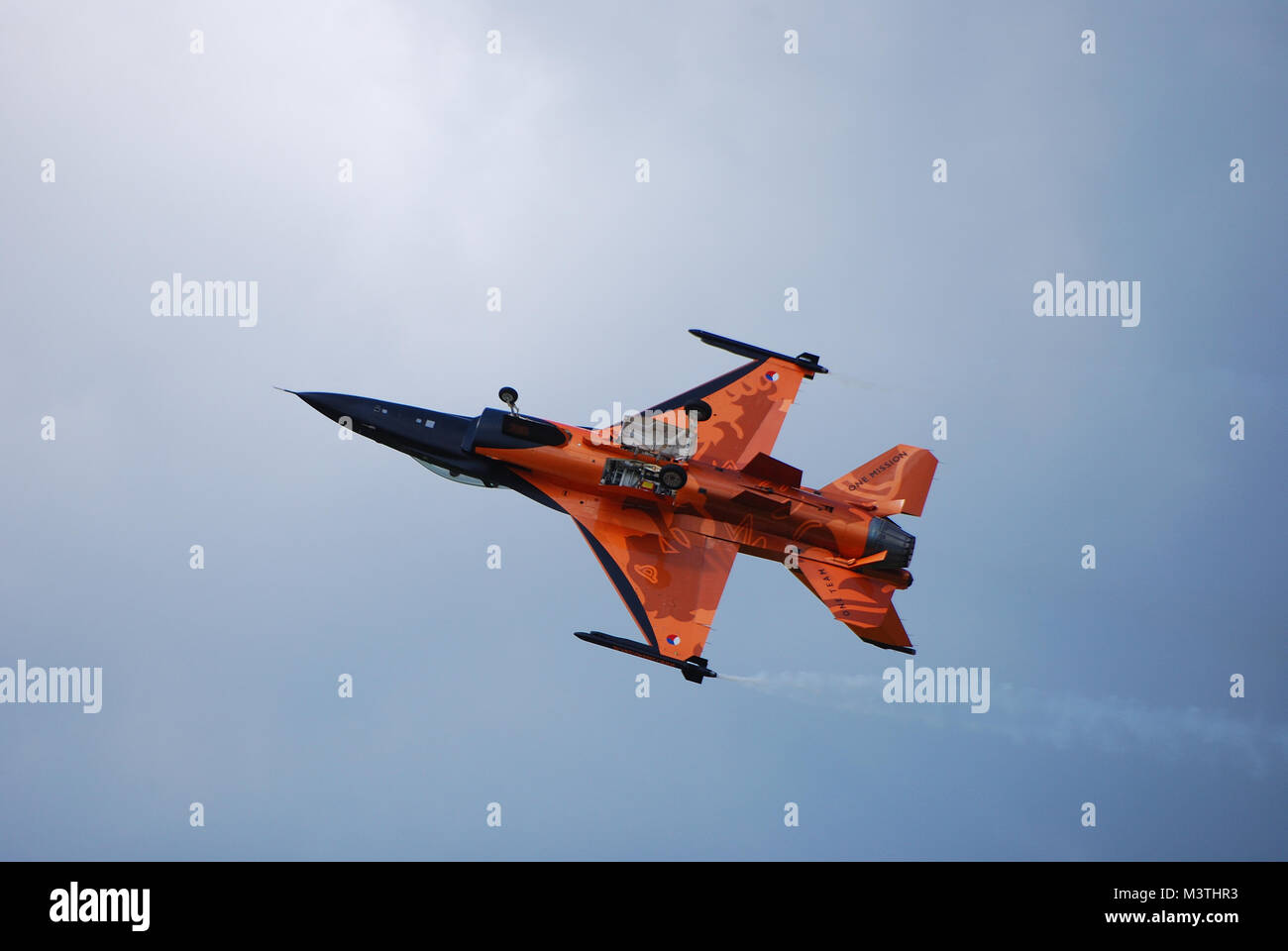 pointed fast orange airplane flies inverted with open flap flugshow - Stock Image