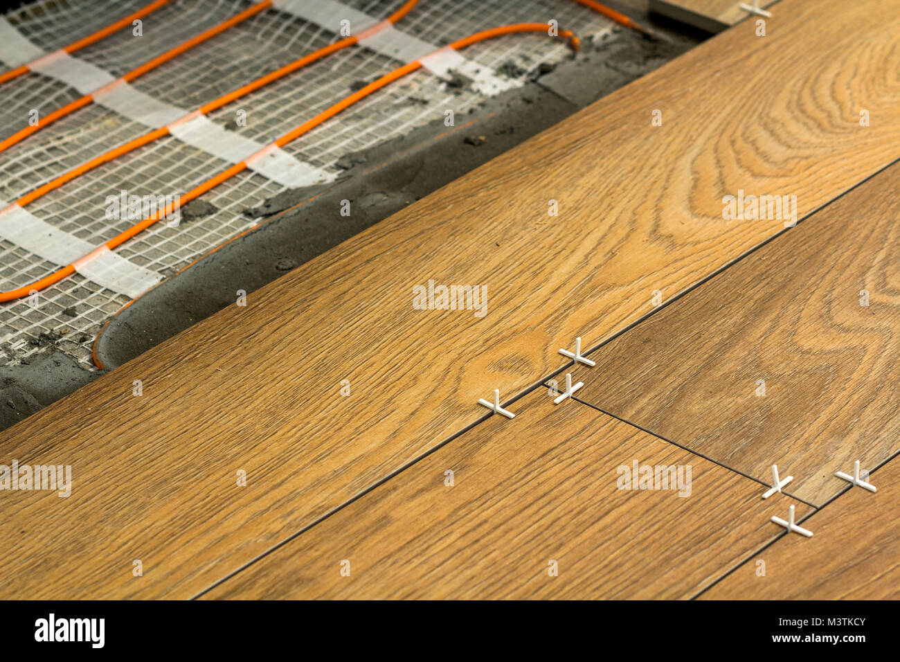 Installation of ceramic tiles and heating elements in warm tile installation of ceramic tiles and heating elements in warm tile floor renovation and improvement concept dailygadgetfo Images