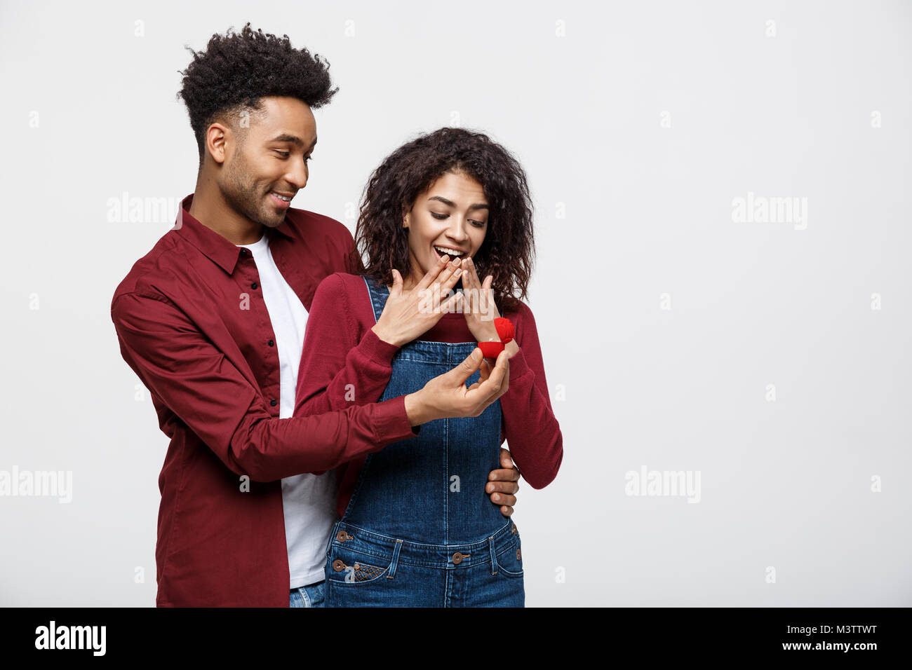 Young handsome african american man surprisingly ask her girlfriend for proposal - Stock Image