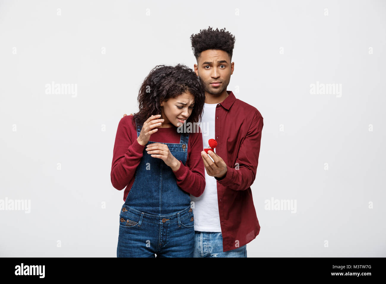 Young African American Scared girlfriend rejecting a marriage proposal. Humorous situation - Stock Image