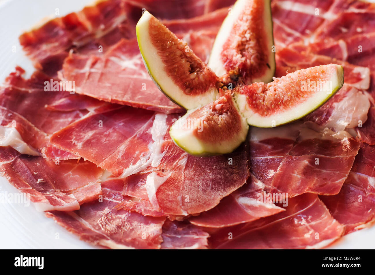 Spanish Cuisine tapas food Jamon with fig. Beautiful appetite slices of raw pork meat, white plate background. - Stock Image