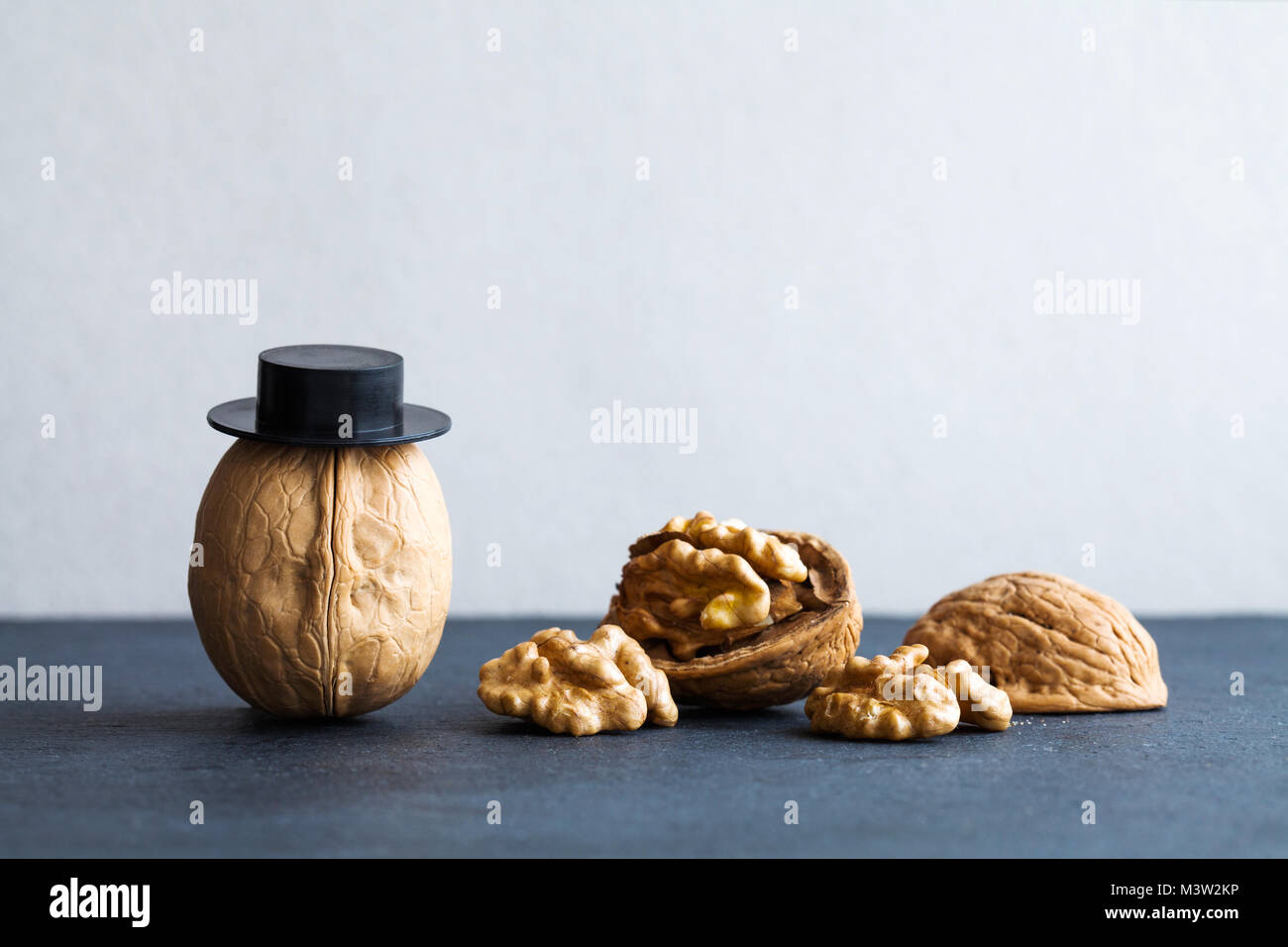 Senor walnuts black hats, half nutshell on stone and gray background. Creative food design poster. Macro view selective - Stock Image