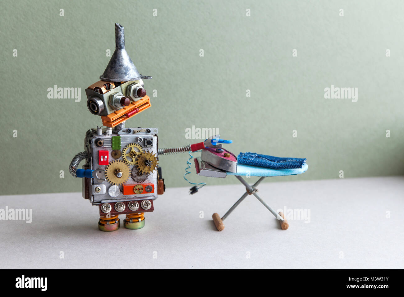 Robot housework assistant ironing blue jeans with iron on the board. green wall gray floor room interior. Creative - Stock Image