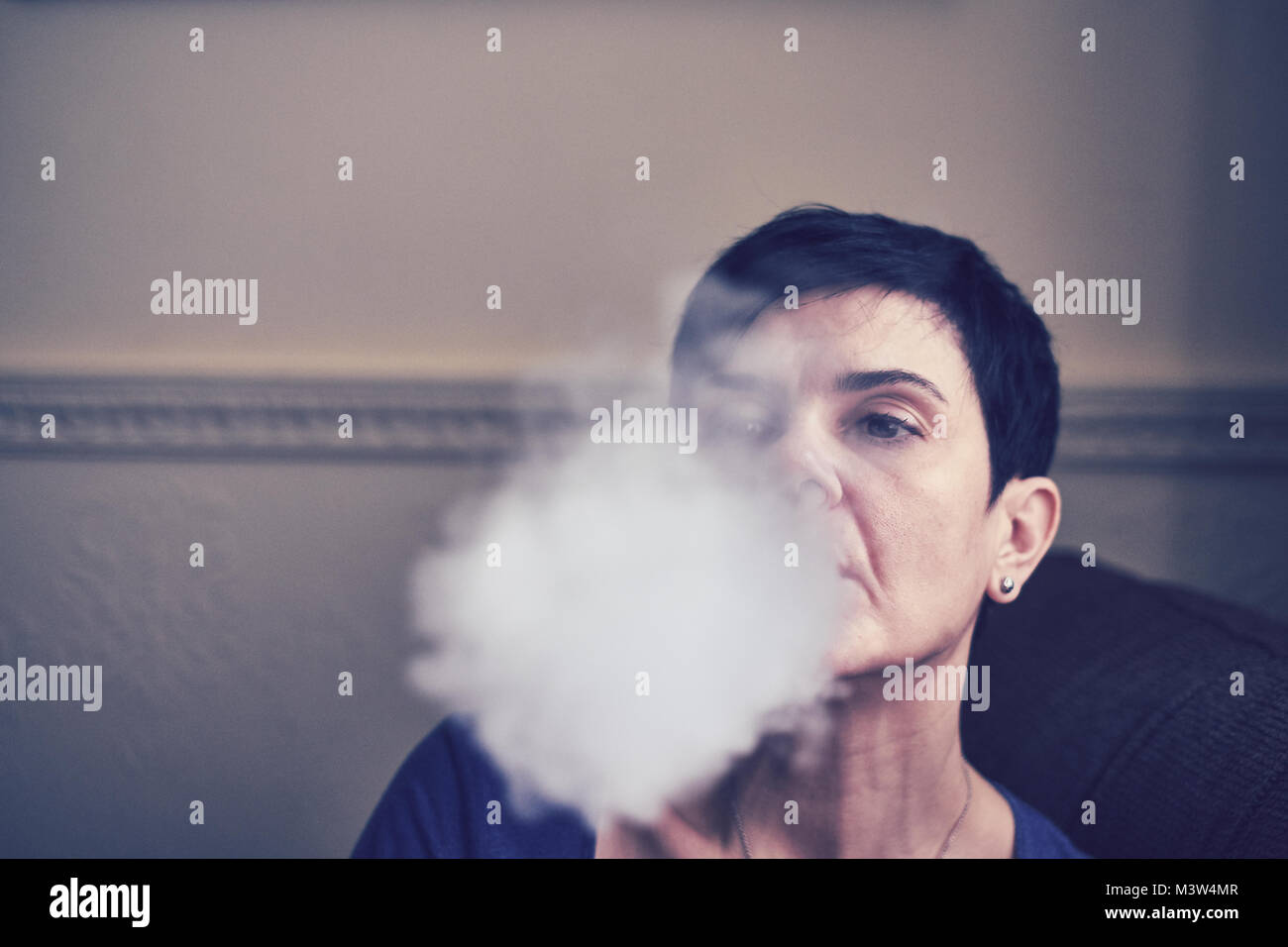 Female with e-cigarette, vaping and re-filling - Stock Image