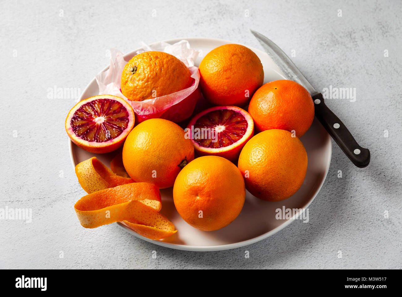 A group of oranges on a plate. some of them cut. knife . on a stone background. a healthy summer table, the preparation Stock Photo