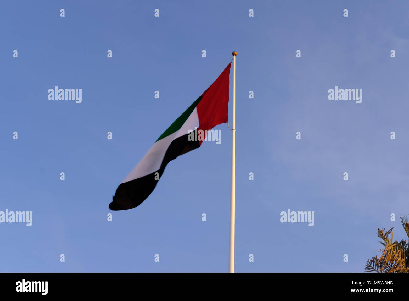 United Arab Emirates Flag waving high in the wind with isolated sky in background Stock Photo