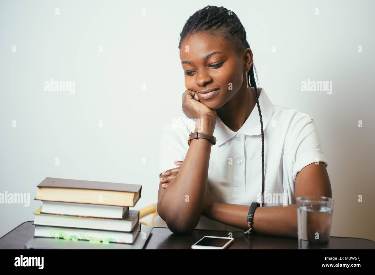 african young woman sitting at table with books at home - Stock Image