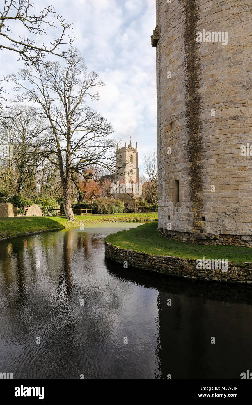 Nunney Castle with the Church of All Saints in the background, Nunney, Somerset, England - Stock Image