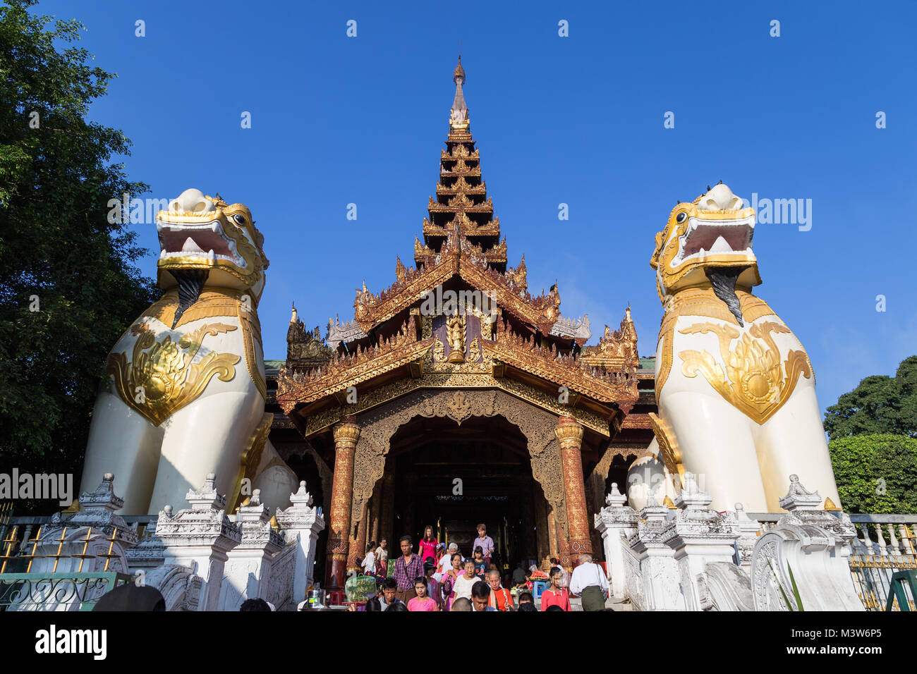 People at the Shwedagon Pagoda's eastern entrance in Yangon, Myanmar. Two giant chinthes or leogryphs (stylised - Stock Image