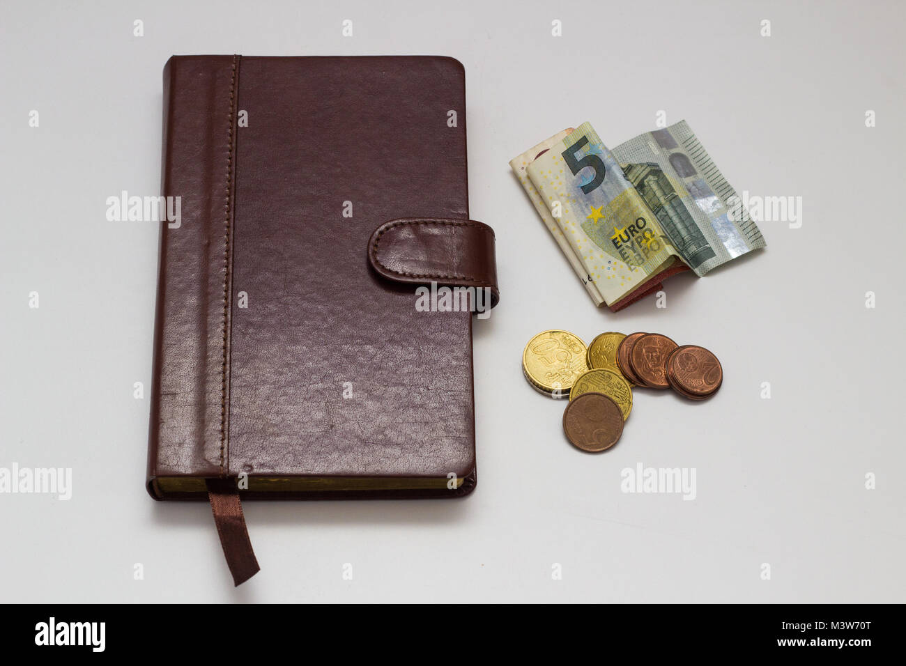 Note book and Euro banknotes and coins on a white background - Stock Image