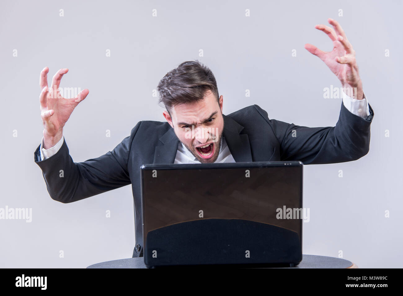 Young businessman angry with his laptop - Stock Image