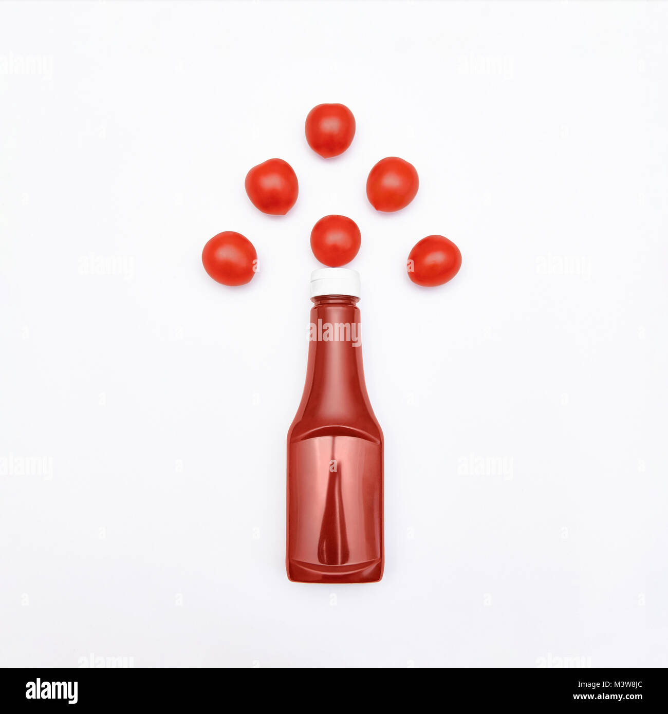 Ketchup Flat lay Bottle of ketchup is lying among juicy cherry tomatoes Photo mockup for advertising with space - Stock Image
