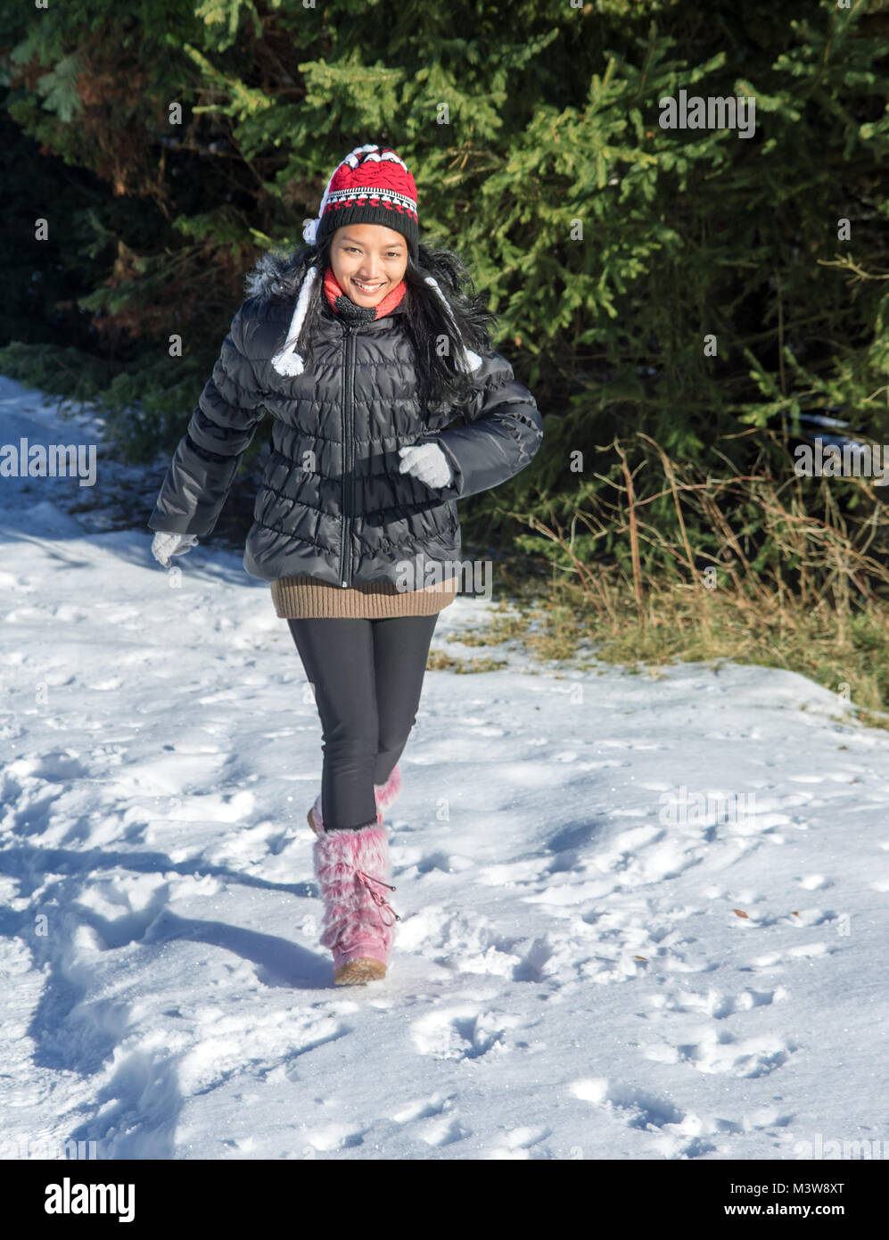 A cheerful woman running in a snowy nature. A joyful girl in winter clothes runs on snow. Outdoor fun in winter. - Stock Image