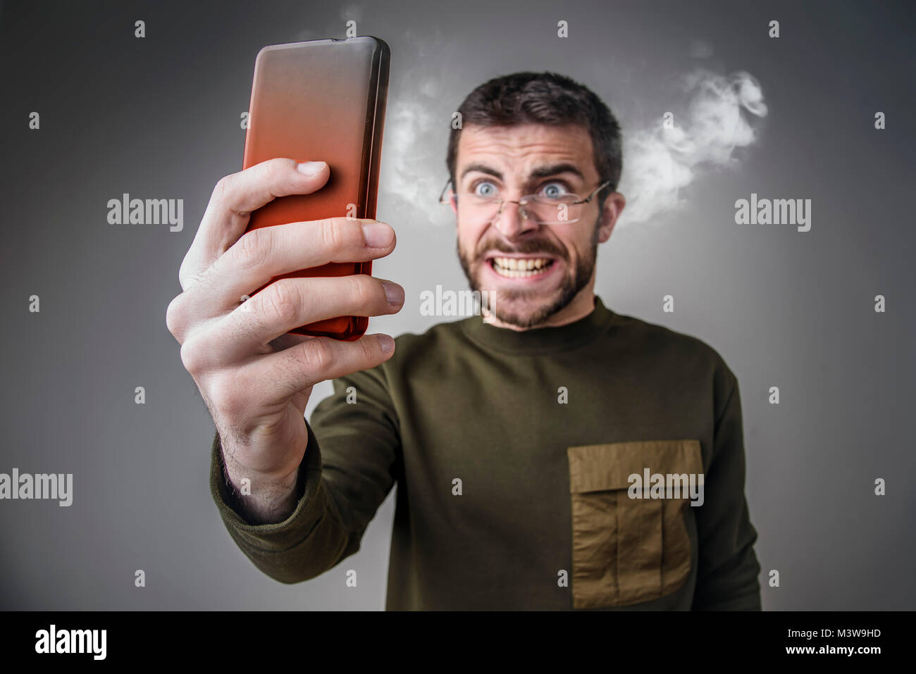 Steaming with rage, man yelling at his phone - Stock Image