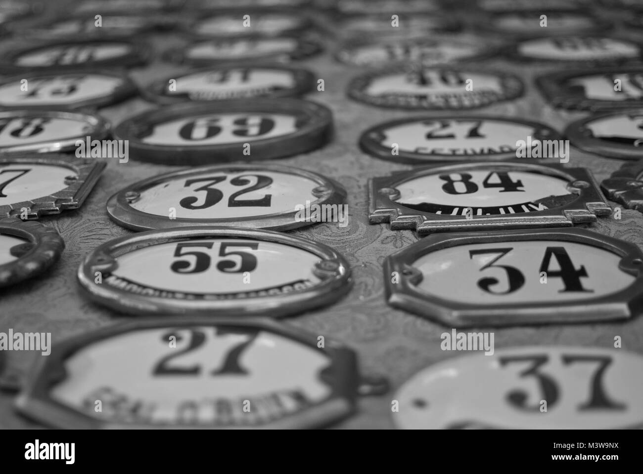 House number plaques arranged in lines on a table at a flea market in Buenos Aires, Argentina - Stock Image