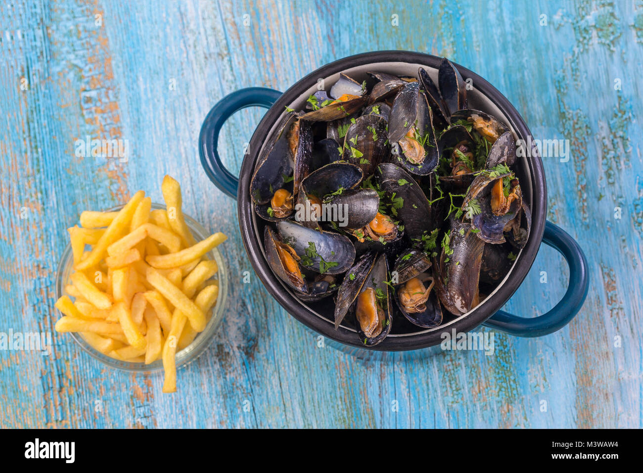 mussels in a blue ceramic pot on a blue wooden background. with a glass bowl of french fries. Meditteranean lifestyle. - Stock Image