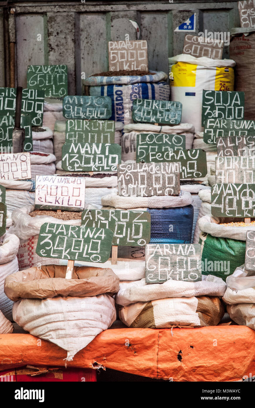 Sacks of nuts and grains, with their names written in chalk, being sold at a market - Stock Image