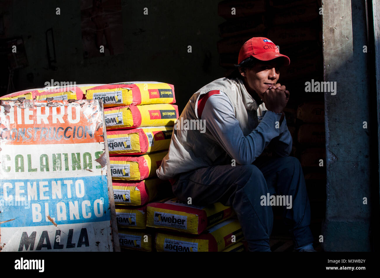 A young man posing while sitting on sacks of cement in Tarija, Bolivia - Stock Image
