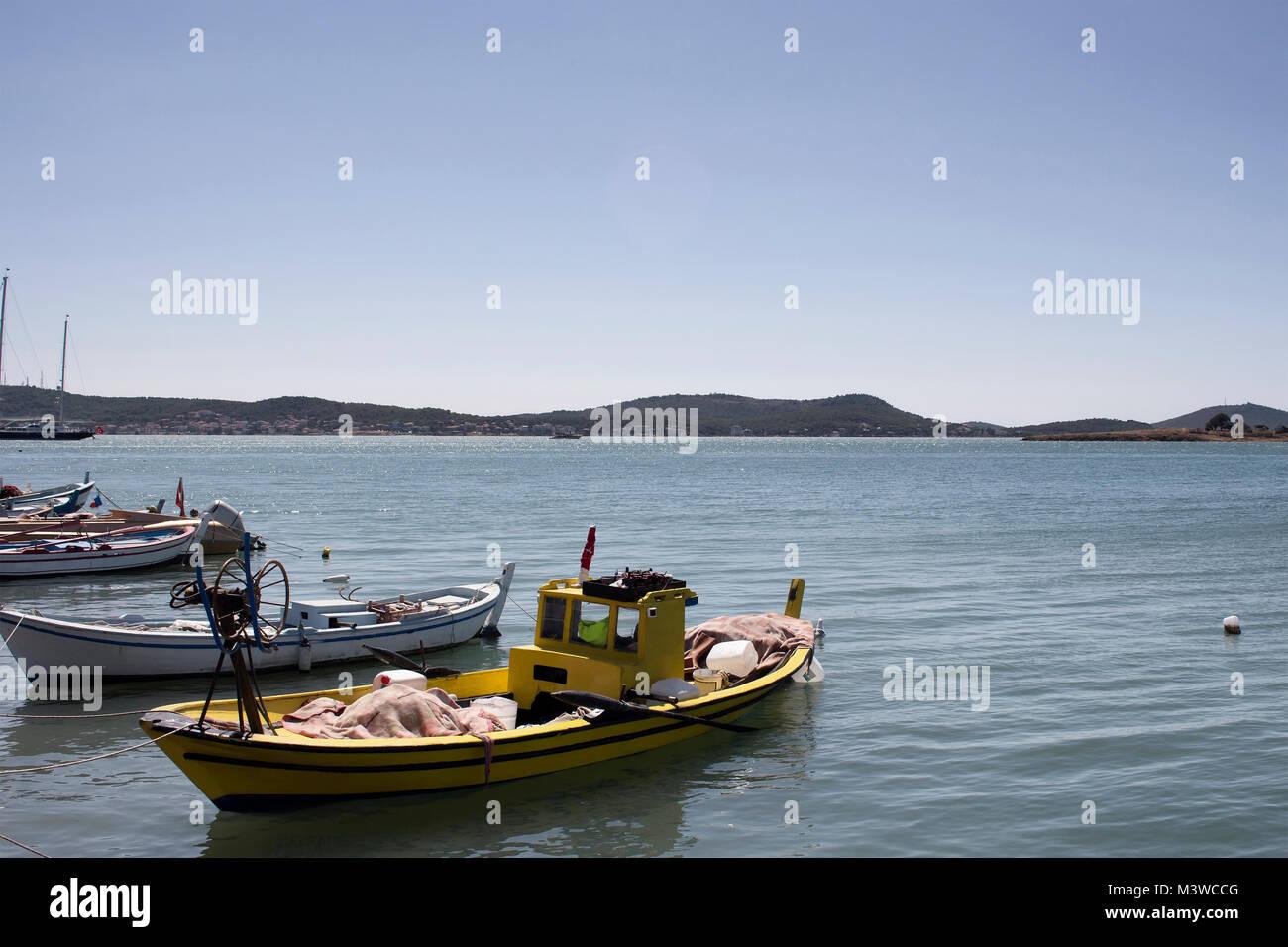 Small, wooden fishing boats and Aegean sea in Cunda (Alibey) island. - Stock Image