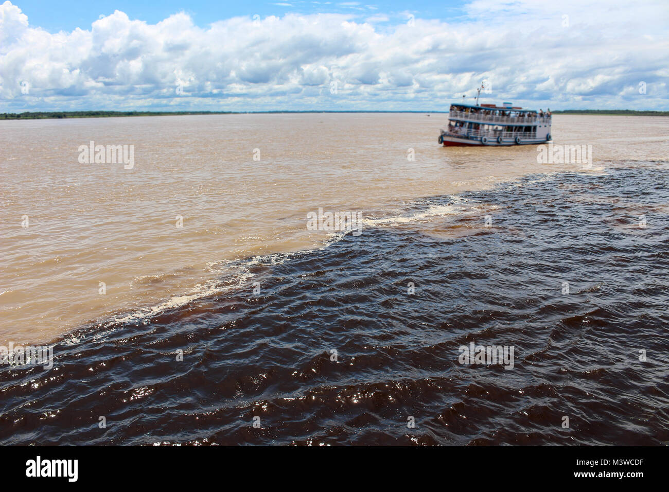 Meeting of the Waters of Rio Negro and the Amazon River or Rio Solimoes near Manaus, Amazonas, Brazil in South America - Stock Image