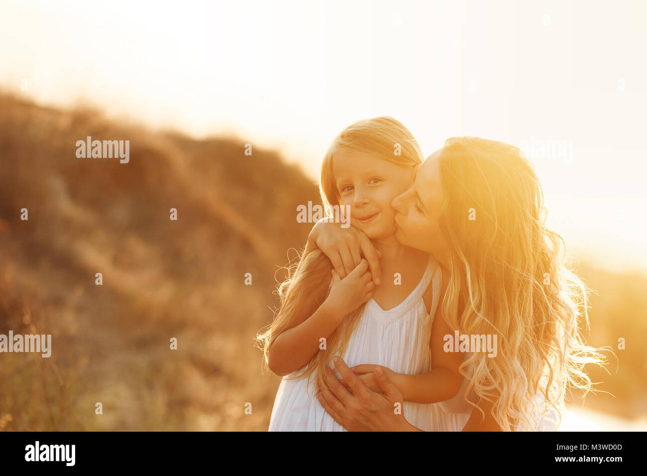 Family, mother and daughter at sunset. The girl bends down and kisses her daughter. Girls in white dresses. They - Stock Image